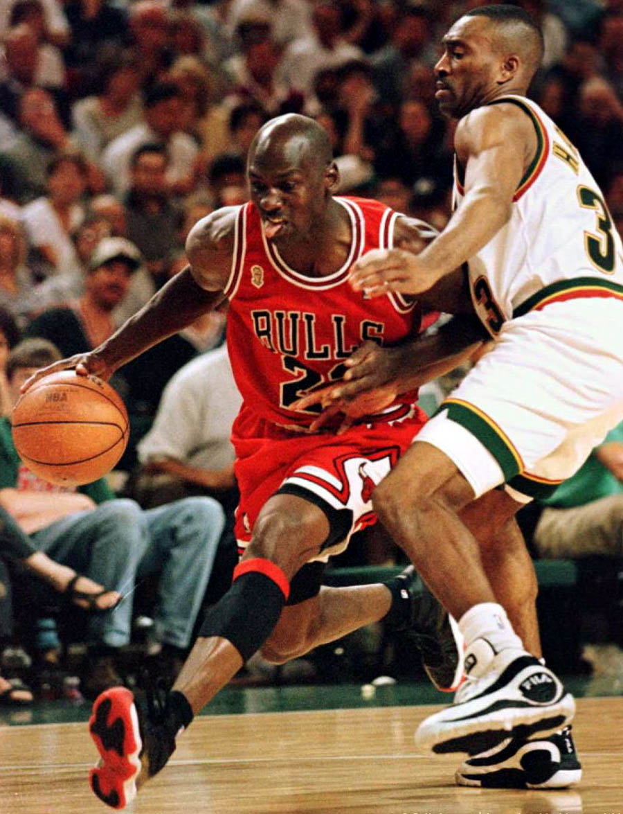 Michael Jordan of the Bulls driving against Hersey Hawkins of the Sonics Defense - while wearing Jordan XI ' Playoffs'